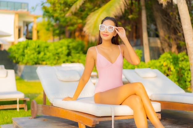 Ontspant de portret mooie jonge aziatische vrouw glimlach geniet van vrije tijd rond zwembad in hoteltoevlucht