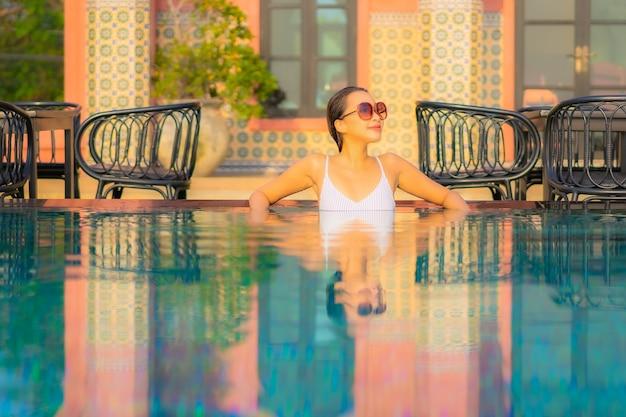 Ontspant de portret mooie jonge aziatische vrouw glimlach geniet van vrije tijd rond zwembad in resorthotel op vakantie