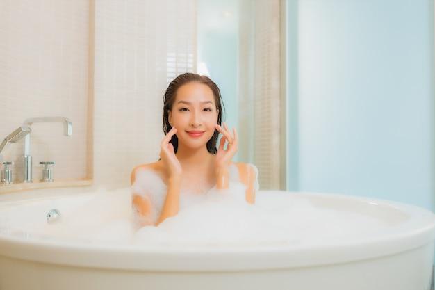 Ontspant de portret mooie jonge aziatische vrouw glimlach in badkuip bij badkamersbinnenland