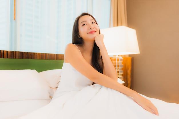 Ontspant de portret mooie jonge aziatische vrouw glimlach op bed in slaapkamerbinnenland