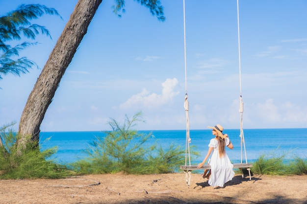 Ontspant de portret mooie jonge aziatische vrouw glimlach op schommeling rond strand overzeese oceaan voor aardreis in vakantie
