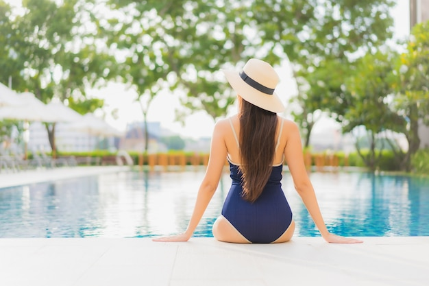 Ontspant de portret mooie jonge aziatische vrouw glimlach rond openluchtzwembad in hoteltoevlucht op vakantiereizen