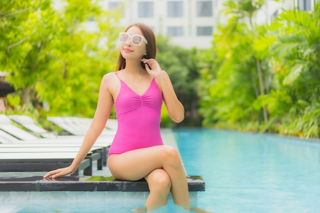 Ontspant de portret mooie jonge aziatische vrouw glimlach rond openluchtzwembad in hoteltoevlucht