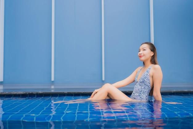 Ontspant de portret mooie jonge aziatische vrouw glimlach rond openluchtzwembad