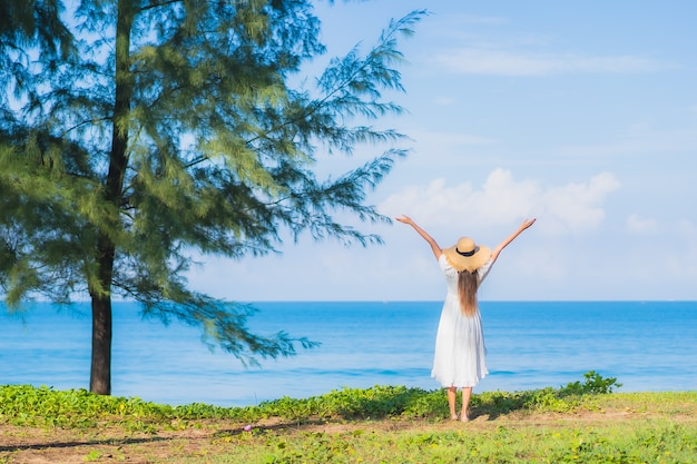 Ontspant de portret mooie jonge aziatische vrouw glimlach rond strand overzeese oceaan met blauwe hemel witte wolk voor reisvakantie
