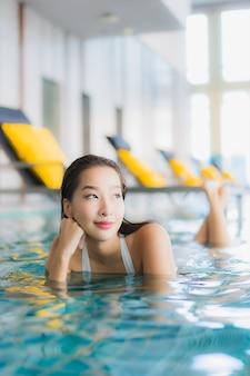 Ontspant de portret mooie jonge aziatische vrouw glimlach rond zwembad in hoteltoevlucht op reisvakantie