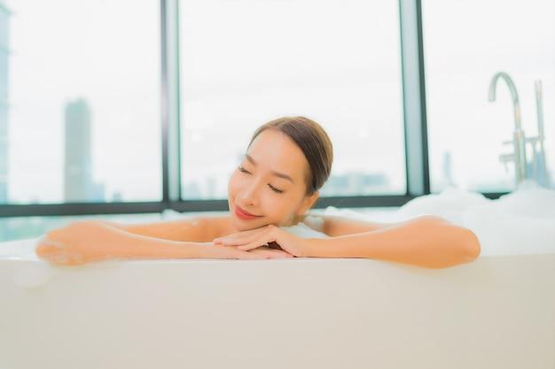 Ontspant de portret mooie jonge aziatische vrouw glimlachvrije tijd in badkuip in badkamersbinnenland