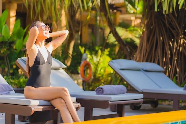 Ontspant de portret mooie jonge aziatische vrouw glimlachvrije tijd rond openluchtzwembad bijna overzees