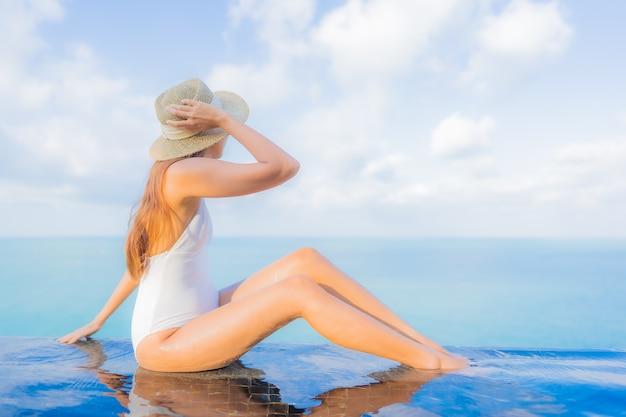 Ontspant de portret mooie jonge aziatische vrouw glimlachvrije tijd rond openluchtzwembad in hoteltoevlucht op reisvakantie