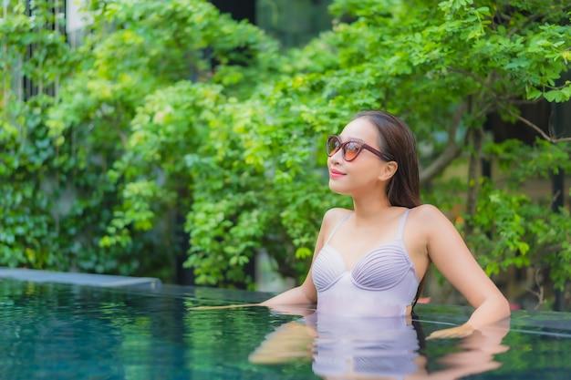 Ontspant de portret mooie jonge aziatische vrouw glimlachvrije tijd rond openluchtzwembad in hoteltoevlucht