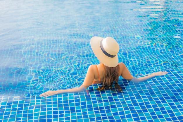 Ontspant de portret mooie jonge aziatische vrouw glimlachvrije tijd rond openluchtzwembad in resorthotel met zeezicht op de oceaan