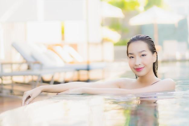 Ontspant de portret mooie jonge aziatische vrouw glimlachvrije tijd rond openluchtzwembad