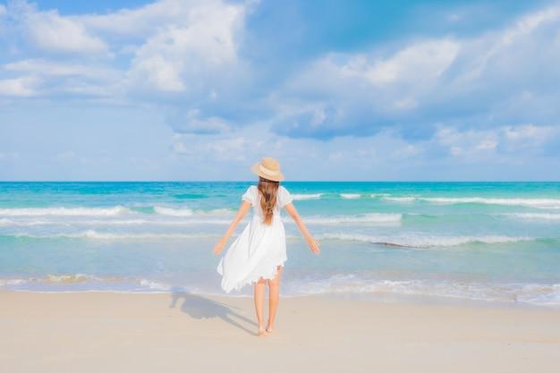 Ontspant de portret mooie jonge aziatische vrouw glimlachvrije tijd rond strand overzeese oceaan in reisvakantie