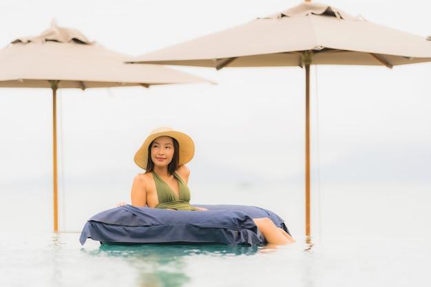 Ontspant de portret mooie jonge aziatische vrouw in luxe openlucht zwembad in bijna het strand overzeese van de hoteltoevlucht oceaan