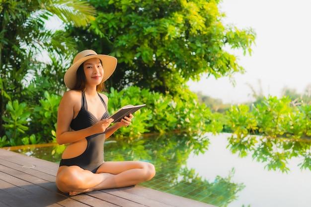 Ontspant de portret mooie jonge aziatische vrouw in zwembad bij hoteltoevlucht voor vrije tijdsvakantie