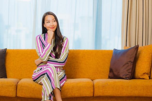 Ontspant de portret mooie jonge aziatische vrouw op bank in woonkamerbinnenland