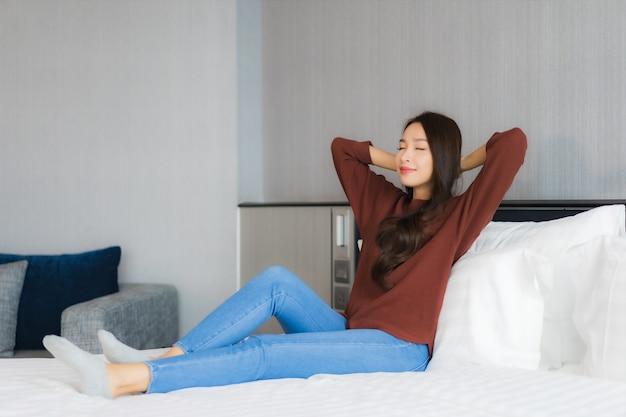 Ontspant de portret mooie jonge aziatische vrouw op bed in slaapkamerbinnenland