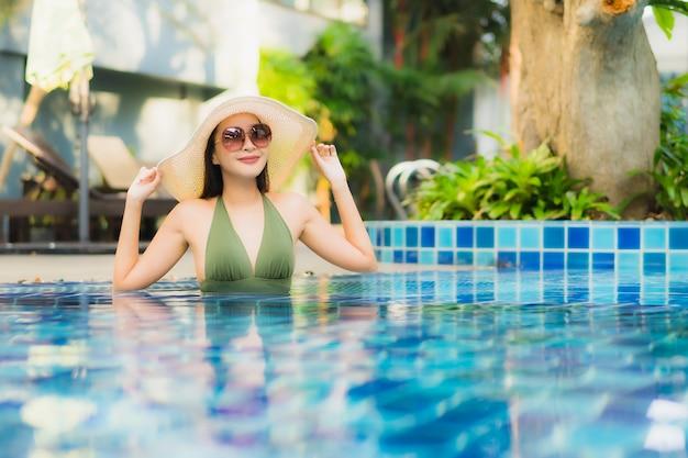 Ontspant de portret mooie jonge aziatische vrouw rond zwembad in hoteltoevlucht
