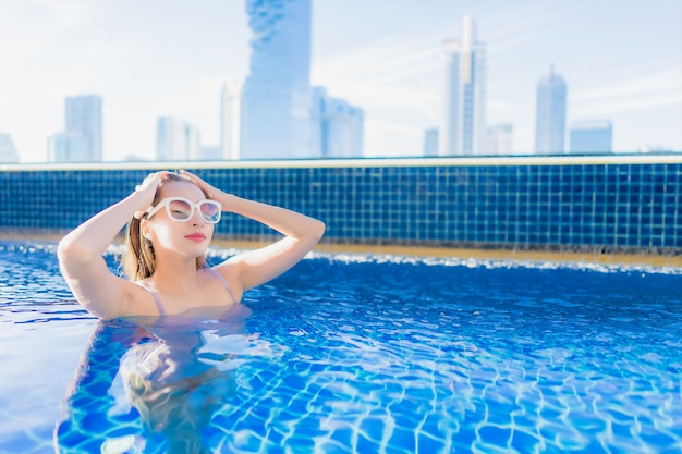 Ontspant de portret mooie jonge aziatische vrouw vrije tijd geniet van rond openlucht zwembad