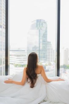 Ontspant de portret mooie jonge aziatische vrouw vrije tijd op bed met stadsmening