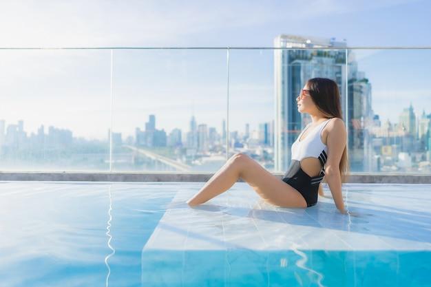 Ontspant de portret mooie jonge aziatische vrouw vrije tijd rond zwembad