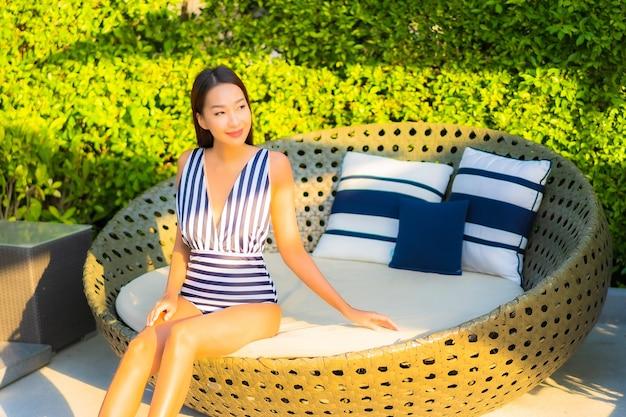 Ontspant de portret mooie jonge vrouw glimlachvrije tijd op vakantie rond zwembad in resorthotel