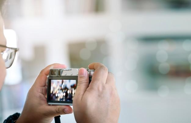 Ontsproten van de mens die foto door digitale camera in openlucht met exemplaarruimte neemt.