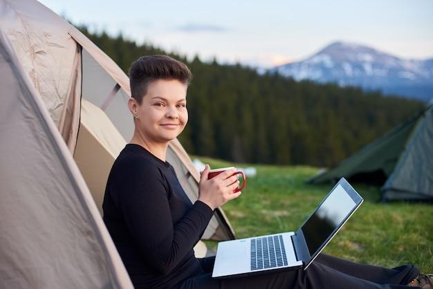 Ontsproten van een gelukkige jonge vrouw die haar drank houdt, die in openlucht ontspant terwijl het kamperen zitting dichtbij de tent met haar laptop