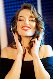 Ontsproten van een vrij jonge vrouw die in hoofdtelefoons met charmante glimlach aan muziek in een studio luistert