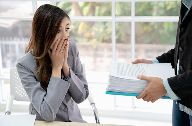 Ontsproten van geschokte jonge onderneemster die bezorgd in het werk van haar werkgever kijkt. verras zakenvrouw.