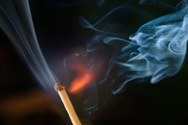 Ontsteking van wedstrijd met rook, geïsoleerd op zwarte achtergrond
