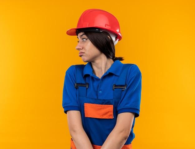 Ontstemd kijkend naar de jonge bouwvrouw aan de zijkant in uniform