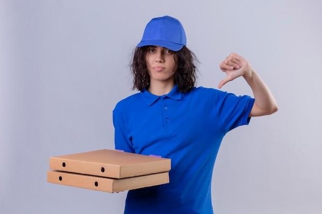 Ontstemd leveringsmeisje in blauw uniform en glb die pizzadozen houden die duimen over witte muur tonen