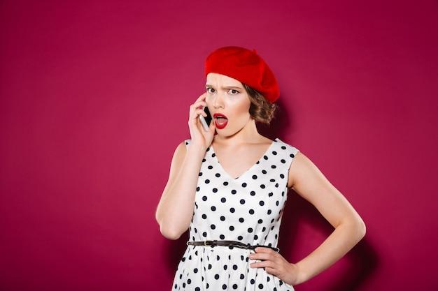 Ontstemde gembervrouw in kleding met wapen op heup die door smartphone spreken en de camera over roze bekijken