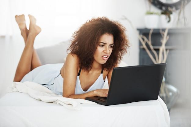 Ontstemde mooie afrikaanse vrouw die in nachtkleding laptop bekijkt die op bed thuis ligt.