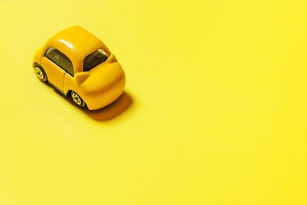 Ontwerp eenvoudig gele vintage retro speelgoedauto geïsoleerd op gele achtergrond