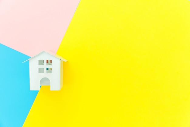 Ontwerp eenvoudig met miniatuur wit speelgoed huis geïsoleerd op blauw geel roze achtergrond