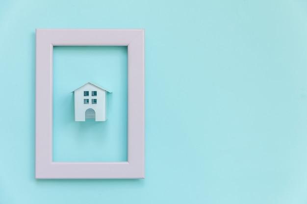 Ontwerp eenvoudig met miniatuur wit speelgoedhuis in roze frame dat op trendy blauwe pastelkleur wordt geïsoleerd