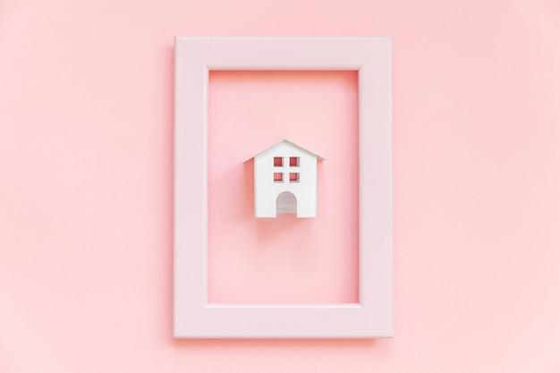 Ontwerp eenvoudig met miniatuur wit stuk speelgoed huis in roze frame dat op roze pastelkleur kleurrijke trendy wordt geïsoleerd