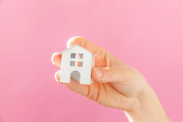 Ontwerp eenvoudig vrouwelijke vrouwenhand die miniatuur wit stuk speelgoed huis houden dat op roze pastelkleur kleurrijke trendy achtergrond wordt geïsoleerd