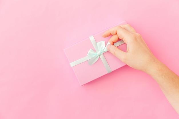 Ontwerp eenvoudig vrouwelijke vrouwenhand die roze die giftdoos houden op roze pastelkleur kleurrijke trendy achtergrond wordt geïsoleerd