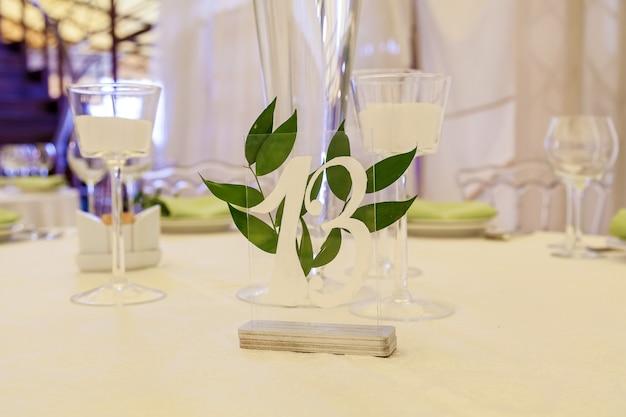 Ontwerp en decordecoratie van het huwelijksfeest met kaarsen van witte rozen, groene bladeren