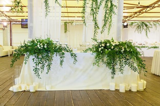 Ontwerp en decordecoratie van het huwelijksfeest met witte rozen groene bladeren c