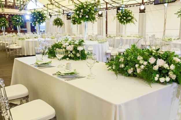 Ontwerp en decordecoratie van het huwelijksfeest met witte rozen, groene bladeren, kaarsen en boeketten met bloemen