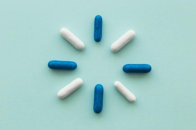 Ontwerp gemaakt met blauwe en witte capsules op lege achtergrond