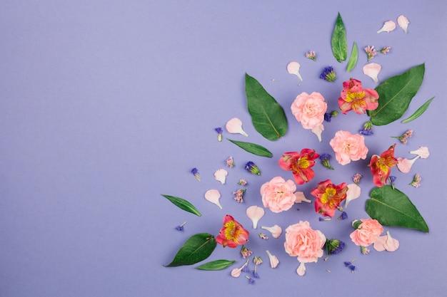 Ontwerp gemaakt van alstroemeria; anjers; bladeren en limonium bloemen op paarse achtergrond