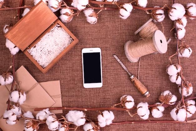 Ontwerp met bloemen met pluizige geschenkdozen van gedroogd katoen, witte smartphone en jute touw over ruwe bruine jute bovenaanzicht kopie ruimte wenskaart