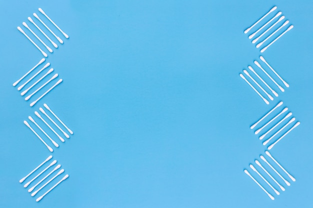 Ontwerp met katoenen zwabbers aan de kant van blauwe achtergrond wordt gemaakt die