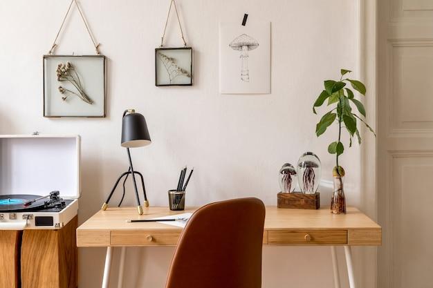 Ontwerp scandinavisch interieur van thuiskantoorruimte met mock-up fotolijsten, houten bureau, bruine stoel, kantoorbenodigdheden en persoonlijke accessoires. stijlvolle neutrale huisstaging. sjabloon.