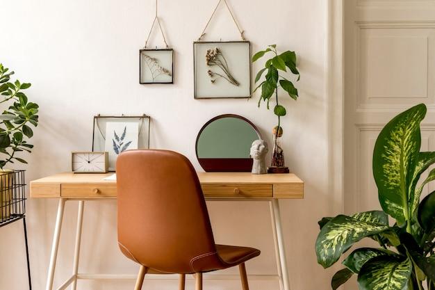 Ontwerp scandinavisch interieur van thuiskantoorruimte met veel mock-up fotolijsten, houten bureau, veel planten, spiegel, kantoor en persoonlijke accessoires. stijlvolle neutrale huisstaging. sjabloon.